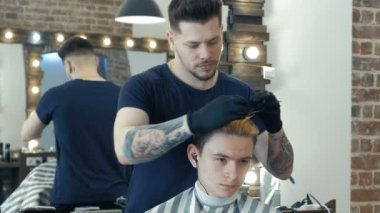 Young guy, teenager, in beauty salon. In process of creating hair style. Professional hairdresser dyeing hair of her client.
