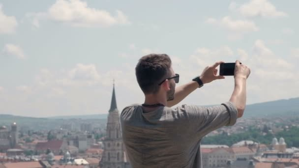 Male traveller make a panoramic photo of the old city to his phone for  Instagram or other social networks  Travel to Romania