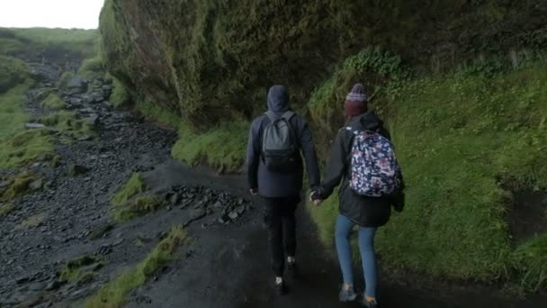A couple hikers Hiking with backpacks walk along a beautiful mountain area holding hands . The concept of active rest.