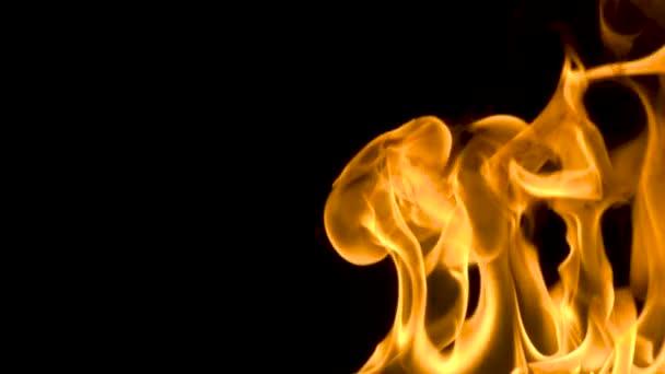 Tűz és lángok égő a fényvisszaverő üveg felületen, fekete háttérrel, lassítva a lángok, lassan mozgó