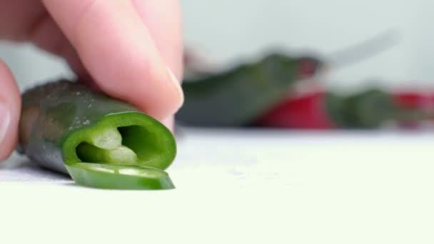 Nasekané zelené papriky s hromadou zelené papriky na wihte sekání boarrd a bílým pozadím. horizontální