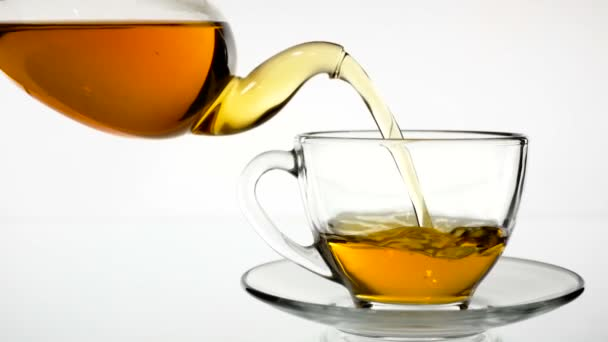 Tea ömlött. Tea, hogy öntenek üveg átlátszó teáscsésze. Tea idő. Átlátszó üveg teáskanna és teáscsésze. Lassú mozgás