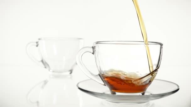 Fekete tea öntenek egy üveg főzőpohárba, az üveg teáskanna. Lassú mozgás. Fehér háttér