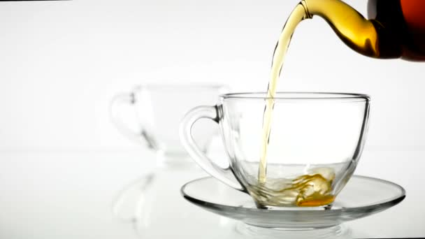 Black tea is poured into a glass beaker from a glass teapot. Slow motion. White background