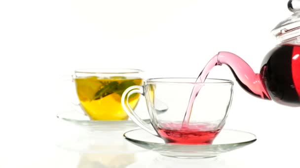 red rose tea in a glass teapot and two cup on a white background.