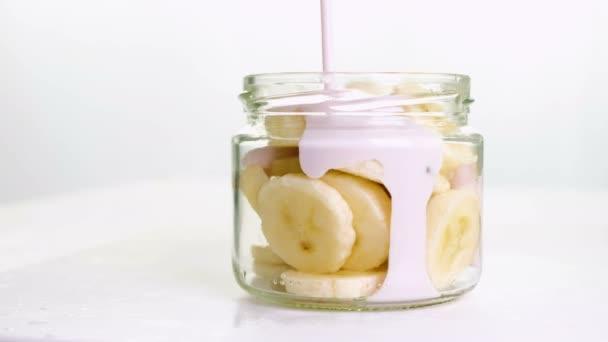 frischer Fruchtjoghurt mit Bananen in einem Glas auf weißem Hintergrund. 4k