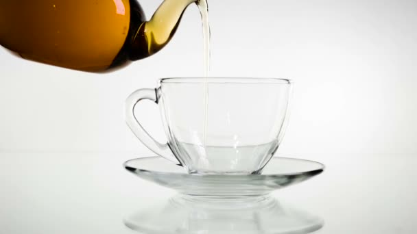 Tea pouring. Tea being poured into glass transparent tea cup. Tea time. Transparent glass teapot and teacup. Slow motion