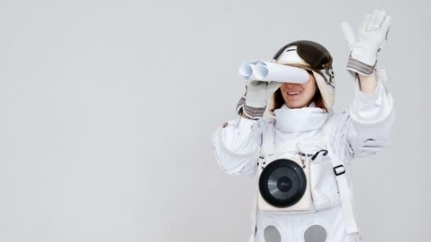 Porträt eines lustigen Astronauten, der im Teleskop in die Ferne blickt. auf weißem Hintergrund.