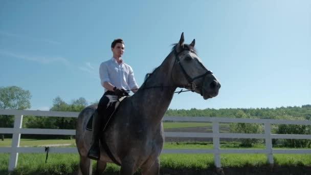 mladý muž jezdit koně Farma zvířat s modrou oblohou v pozadí. Zpomalený pohyb