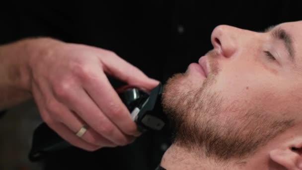 Holič holí klientům vousy na židli. Ostříhat vousy. Holič si holí vousy elektrickým holicím strojem. Pečování o skutečného muže
