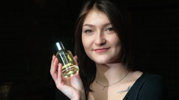 Portrait of a beautiful girl with a perfume bottle