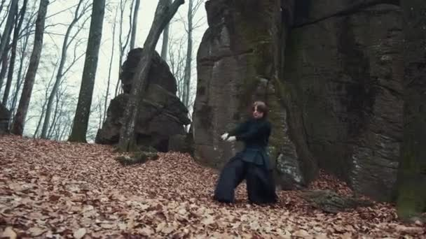 man in traditional Japanese clothes, with a sword, a katana, trains martial arts in the forest background