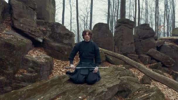 Konzentrierter Mann mit einem japanischen Schwert, einer Katana, die in einem Kiefernwald Iaido praktiziert. Weitwinkel. zurück.