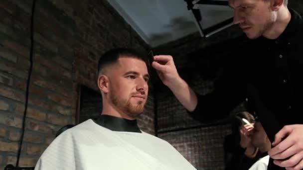 Mans hajvágás fodrász ollóval és fésülködni fodrászati logó mögött lassított felvételen. Férfi kéz, hogy férfi frizura szalonban