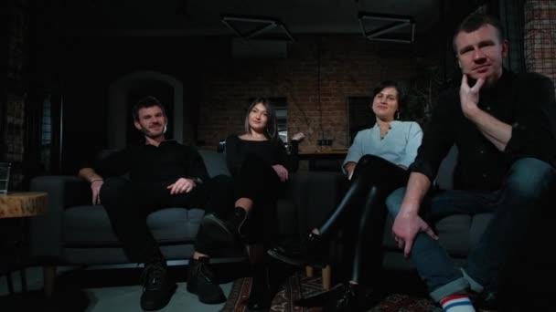 fröhliche Jungs und Mädchen sitzen mit Tassen in der Hand auf dem Sofa.