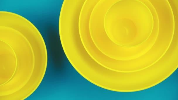 Lapos, sárga csészék türkiz háttéren. Kemény pasztell színek. Minimalista design stílus.