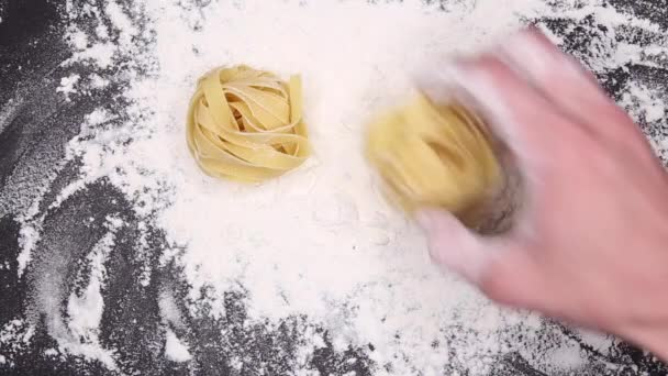 Raw pasta falls onto sifted flour. Pasta on a background of flour and a black table