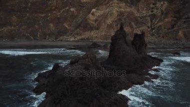 Aerial of the ocean waves washing up on a black basalt rock in Tenerife