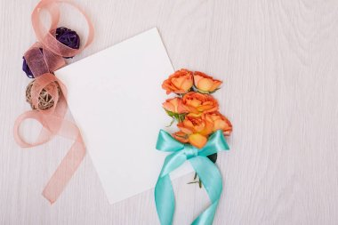 Creative mock up with a card and orang rose. Empty sheet of pape
