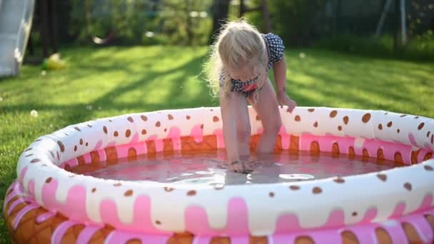 kleines Mädchen spielt im Sommer im aufblasbaren Kinderpool im Garten