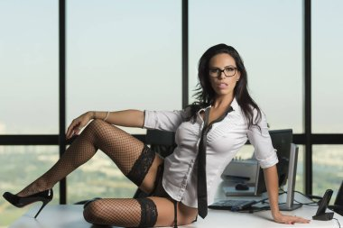 Beautiful secretary sitting on desk in underwear with glasses, white shirt and black neck tie