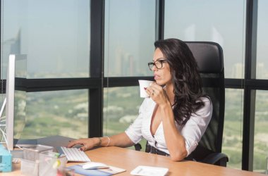 Beautiful Secretary or business woman in office with glasses sipping tea while at computer