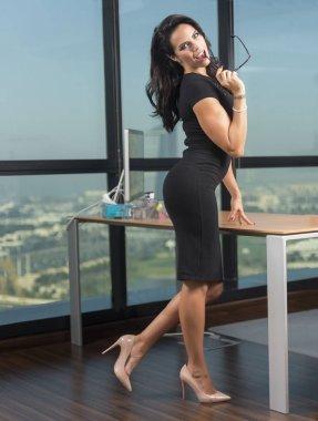 secretary in black dress in office