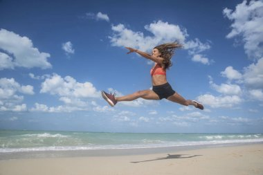Girl dancing leaping on a white sandy beach on a bright sunny day with blue skies and white clouds