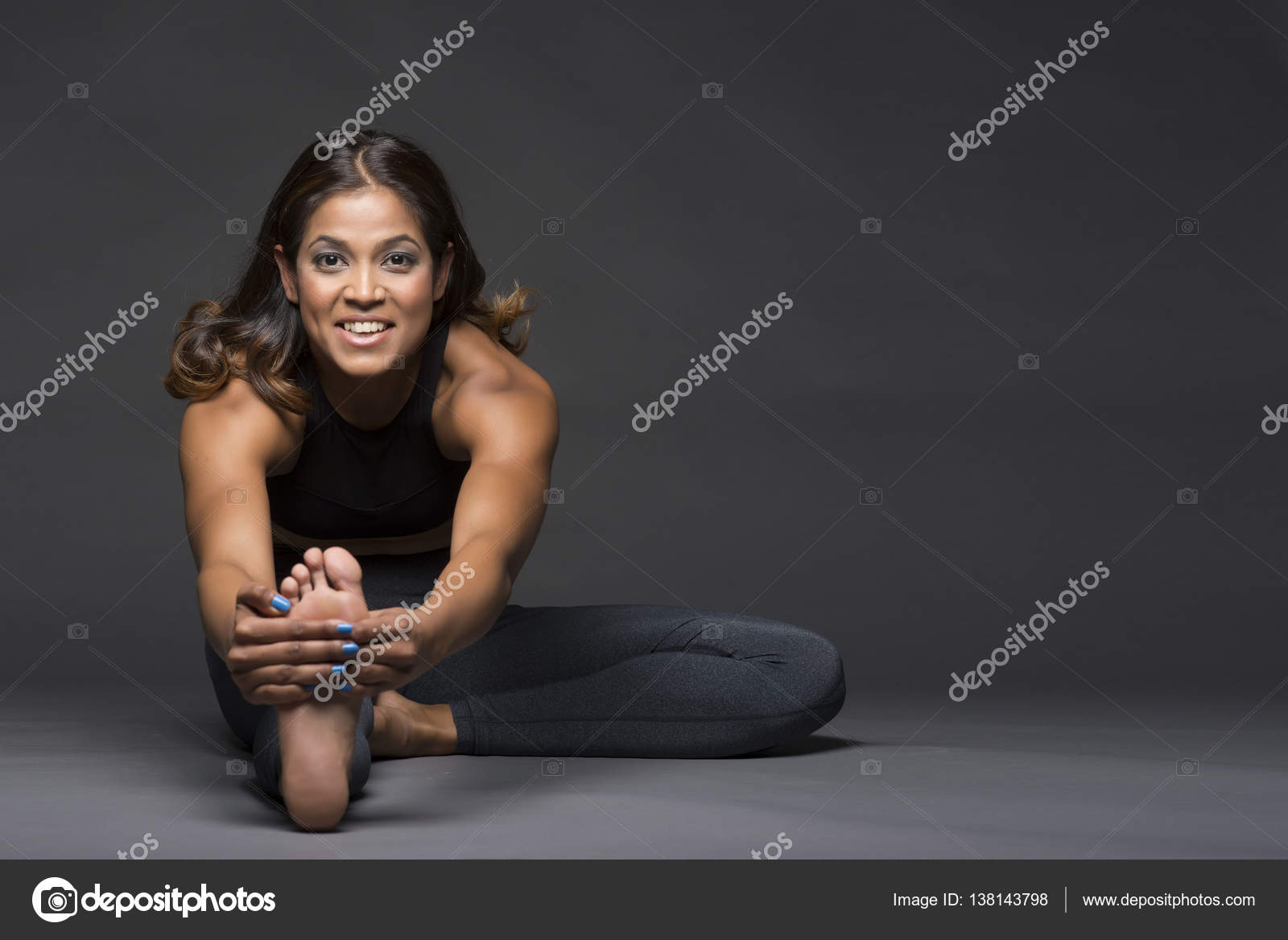 Beautiful Indian Woman In A Yoga Stretch Pose Smiling And Looking At The Camera Stock Photo C Paiken 138143798