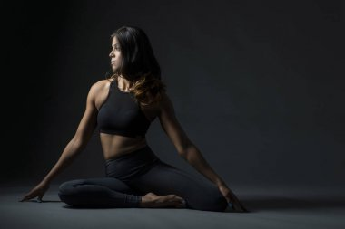 Beautiful Indian woman in yoga pose looking to the side