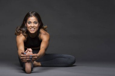 Beautiful Indian woman in a yoga stretch pose, smiling and looking at the camera