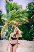Beautiful girl smiling at camera at beach