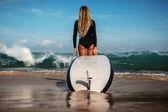nő a szörfözés fedélzeten állva beach