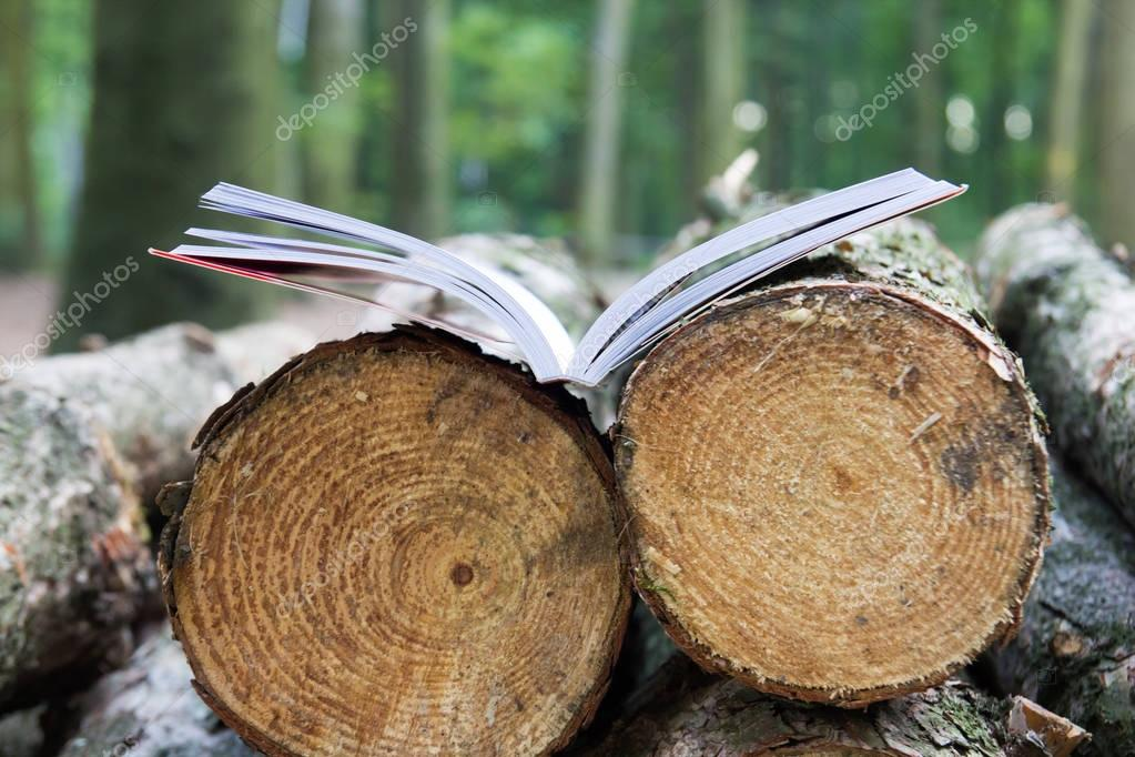 An open book lies on felled trees, Save the trees - read e-books