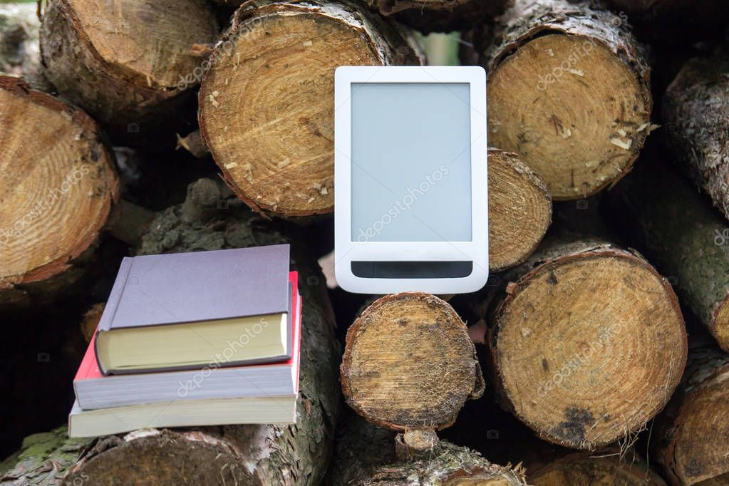Paper books and e-book on the background of felled trees - Save