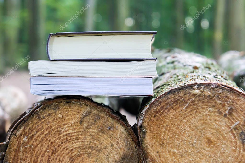 Three books lying on felled trees,  Save the trees - read e-book