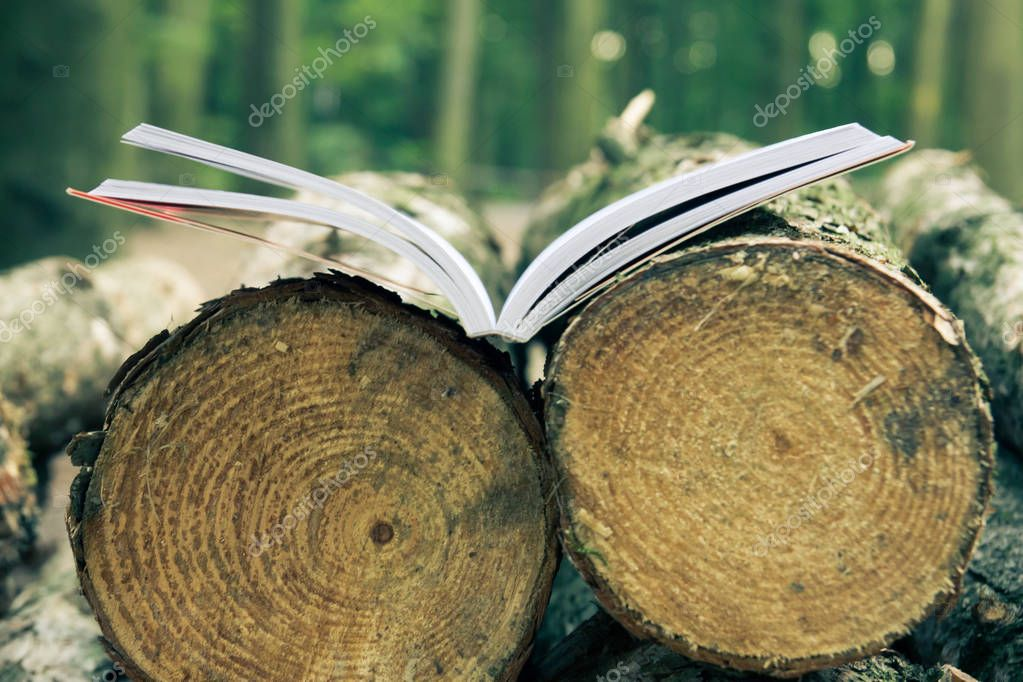 An open book lies on felled trees save trees - read ebooks
