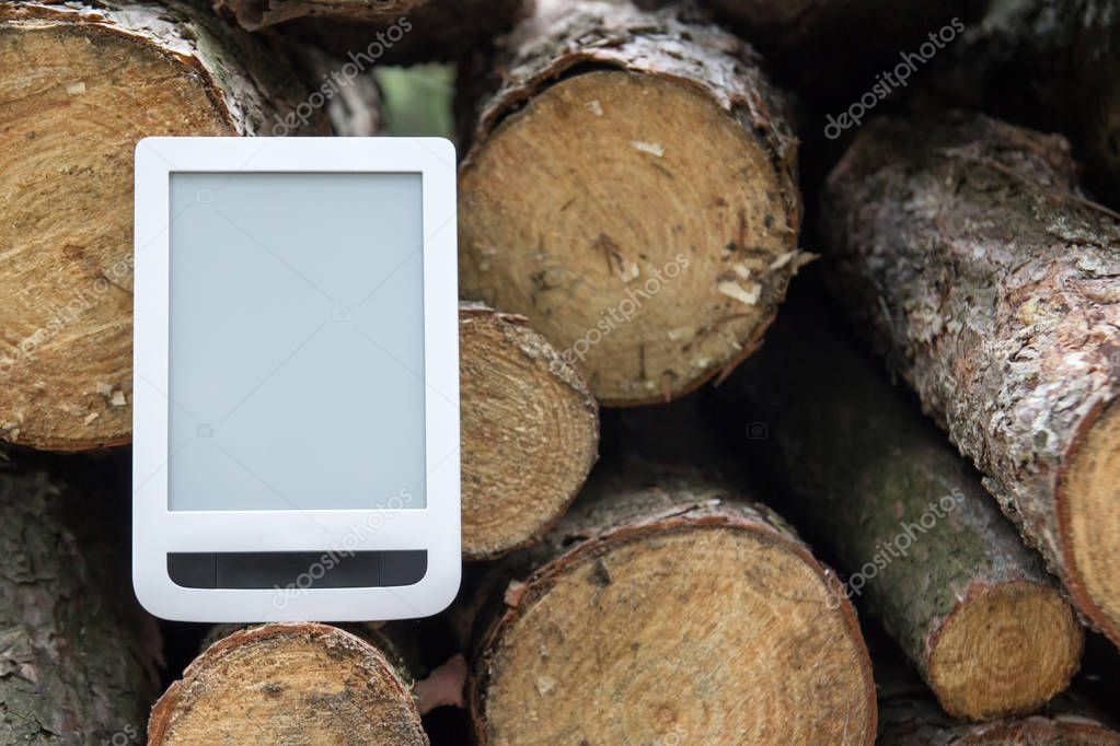 E-book on the background of felled trees, save trees - read e-bo