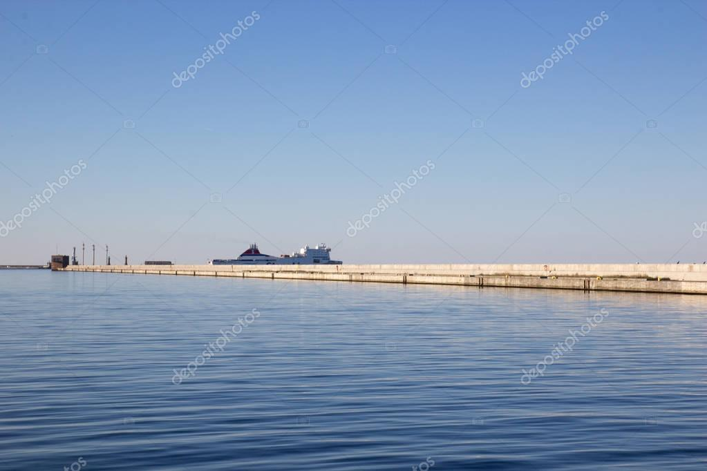 Concrete breakwater and white cruise liner