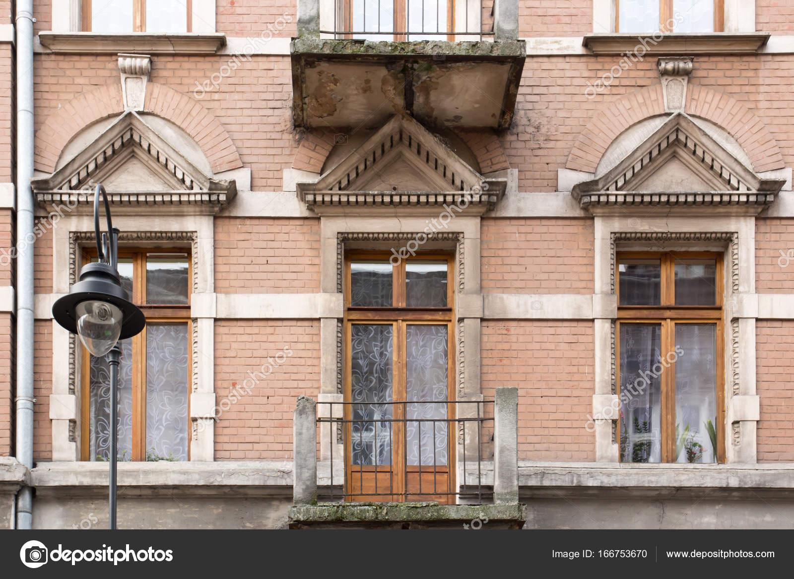 De gevel van het oude huis met het balkon en straat lamp