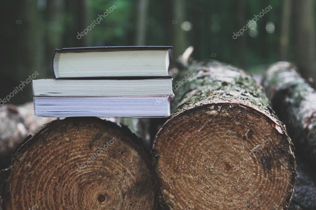 A stack of books lying on the logs,  save trees - read ebooks co