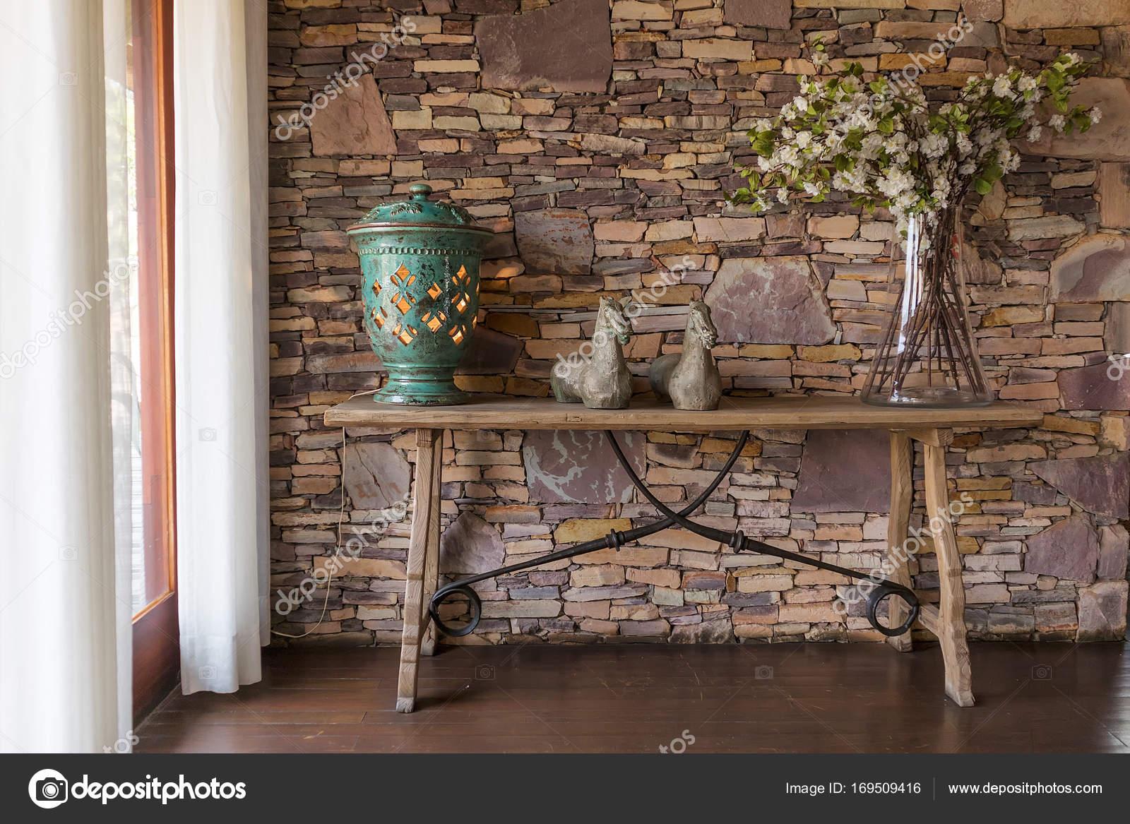 Woonkamer met decoratieve tabel, stenen muur achter — Stockfoto ...