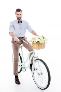 Young man riding hipster bicycle with flower basket and looking at camera  isolated on white stock vector