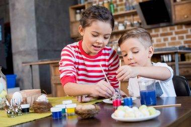 Kids painting easter eggs
