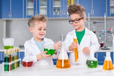 Smiling little boys in lab coats making experiment in chemical laboratory stock vector