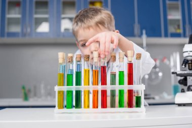 Little boy in chemical laboratory choosing reagents in test tubes stock vector