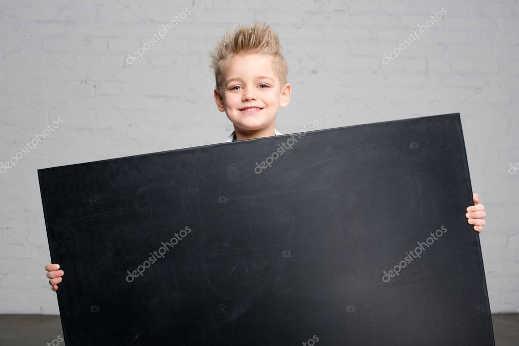 Boy holding blackboard