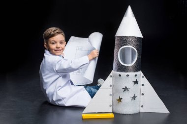 Little boy in white coat holding blueprint while sitting near toy rocket and smiling at camera stock vector