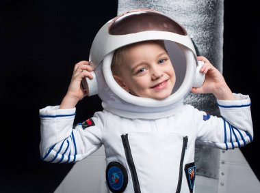 Little boy astronaut in space suit adjusting helmet and smiling at camera stock vector