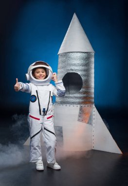 Smiling little girl in astronaut costume standing near launching rocket and showing thumb up stock vector